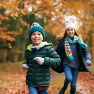 two children run through fallen autumn leaves in woodland