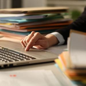 Person reviews professional negligence claim paperwork on desk with a laptop