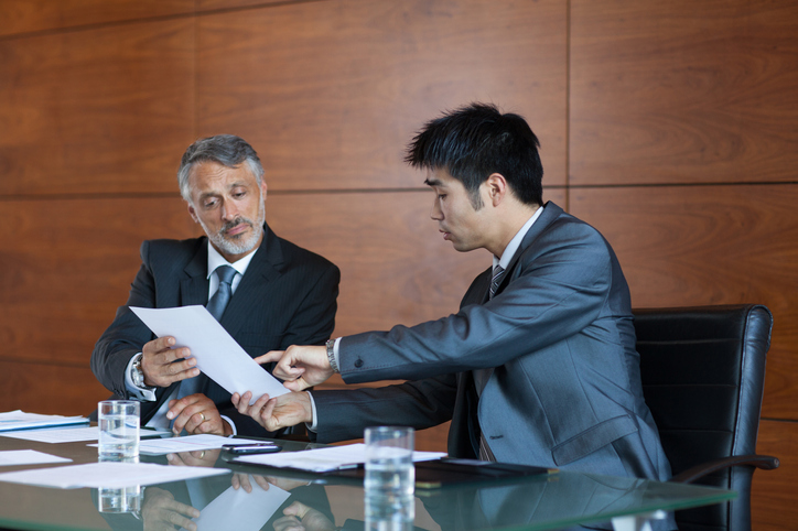 Two business people sitting down to discuss employers business sale review paperwork