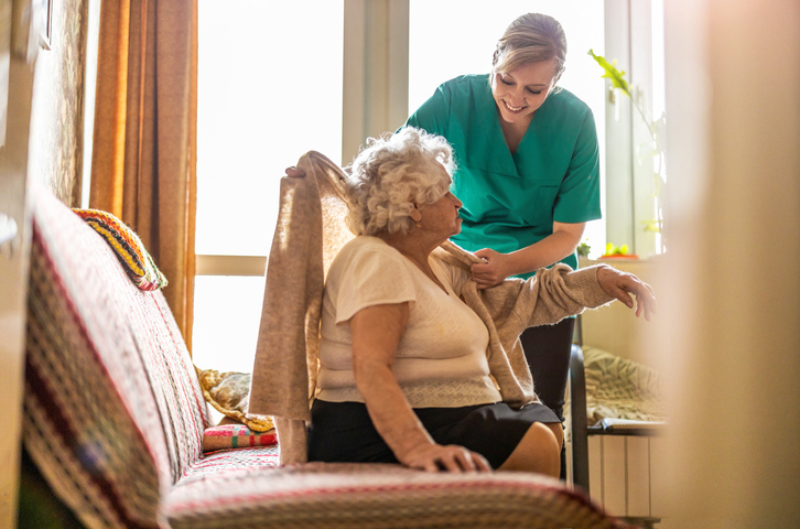 elderly person and carer in care home under cqc warning notice