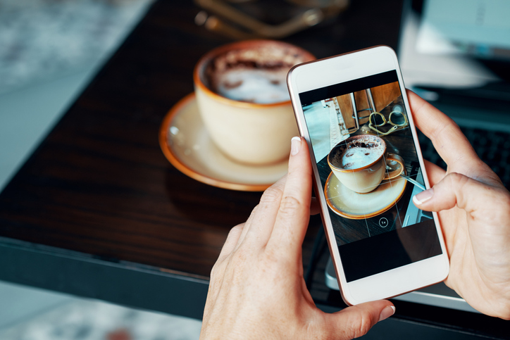 food and drink blogger taking picture of cup of coffee on smart phone