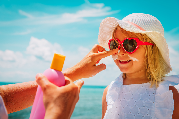 on holiday abroad, mother puts suncream on daughter's face at the seaside. girl wears red sunglasses and white hat