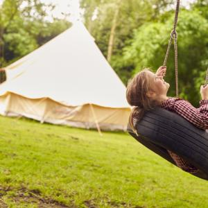 A child on a tyre swing in front of a yurt in a field, holiday accommodation