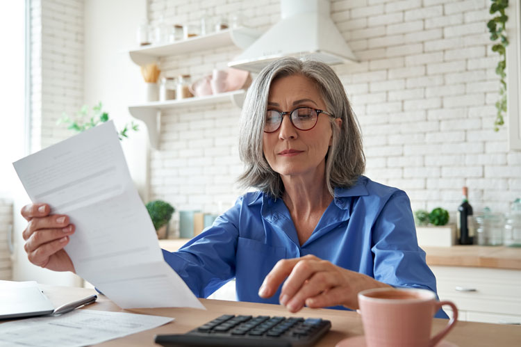 person holding paperwork about their entitlement to spouses pension on divorce using calculator