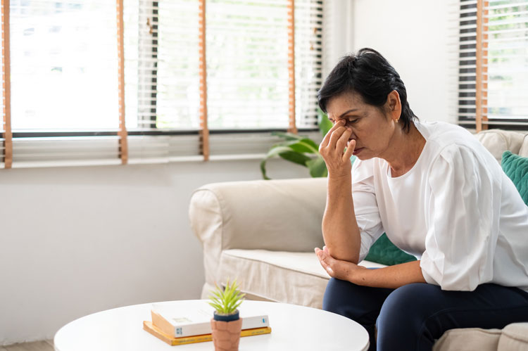 person sitting on sofa concerned about unfair pension distribution in divorce